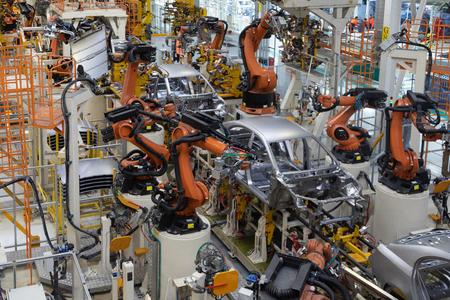 Tecnología moderna de montaje de automóviles. La planta de la industria automotriz. Tienda para la producción y montaje de máquinas vista superior. El proceso de soldadura de partes del automóvil. Foto de archivo