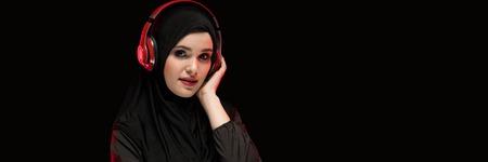 Attractive confident positive friendly muslim arabian woman dressed in black hijab standing in studio looking in camera advertising headphones