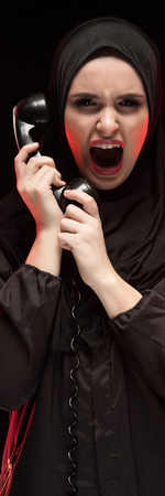 Attractive confident serious upset frightened desperate muslim arabian woman dressed in black hijab standing in studio looking in camera bewildered holding phone asking for help Stock Photo