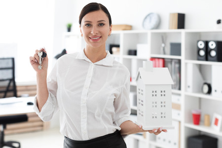 Beautiful young girl working in a bright office. She has dark hair. She's wearing a white shirt. photo with depth of field