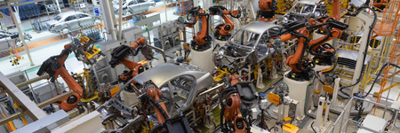 Assembly line production of new car. Automated welding of car body on production line. robotic arm on car production line is working. Wide format shooting automotive. Car factory banner