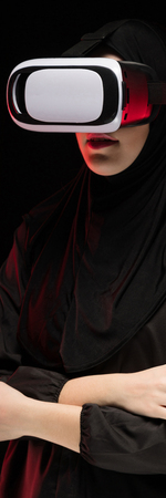 Attractive confident friendly muslim arabian woman dressed in black hijab standing in studio looking in camera in virtual reality glasses device