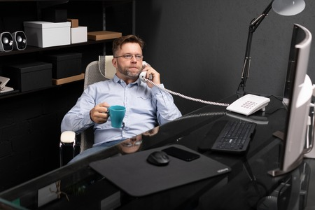 representative man with facial hair in gray shirt and jeans works in modern office at computer. Businessman drinking coffee and answering call on landline. Portrait of entrepreneur at work in office