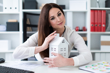 Beautiful girl working in a bright office. Before her on the table is the layout of the house. The girl is dressed in a business suit. She has long dark hair and beautiful makeup. photo with depth of field. The photo depth of focus, a dedicated focus on the hands.