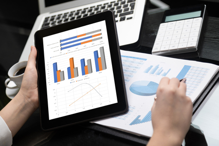 girl points the pen to chart in financial document and holds black tablet with blank screen. Financial report with pie chart and womans hands with tablet. insurance agent gets acquainted with statistics