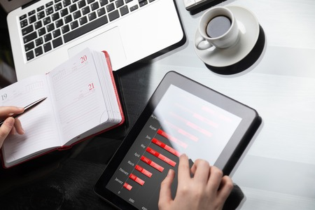 Womans hands with diary and tablet on wooden table. concept of working business place. employee fills diary next to digital tablet computer on background of black office Desk