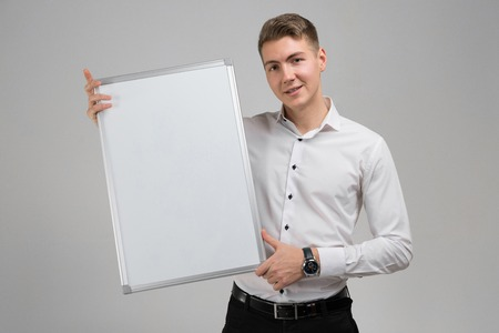 Young businessman with white poster in his hands. Business young man in white shirt in bright Studio alone. place for label
