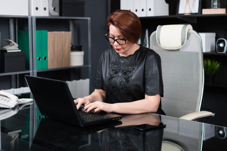 lawyer works at laptop computer in stylish office. Authoritative woman typing on laptop computer in his office. Businesswoman conducts reception in stylish office