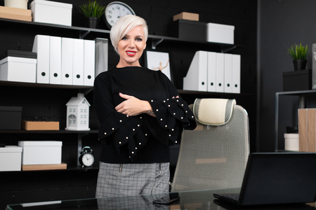 Portrait of stylish young girl in modern office. Businesswoman standing near desktop in his office. Womens place in concept of modern business Stock Photo