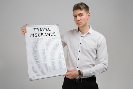 Portrait of a young man in a bright shirt with a poster of travel insurance in his hands in isolation in light of the Studio. Concept meaning Be prepared for emergencies. travel insurance form. insurance policy