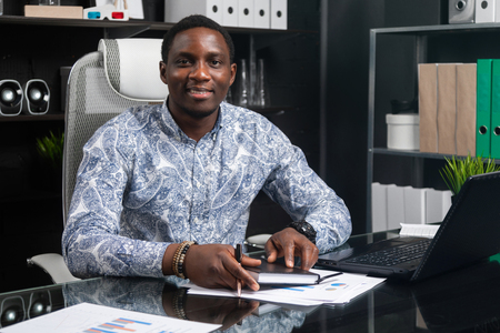 successful young African man sits at his Desk in office and works with charts and diagrams. African-American financier working on project. Business concept in modern world
