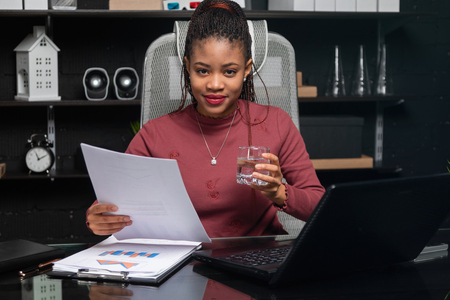 Bright young African girl working in bright office. Portrait of a charming leader with glass of water at work. Business concept in modern world