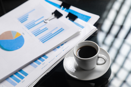 Business documents with graphs and charts are on the table next to a Cup of coffee. Can be used as a business background. Calculation and analysis of the financial results