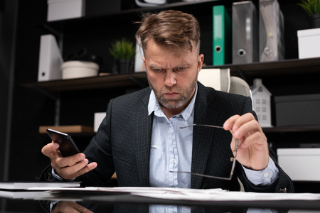 serious man works with business papers and mobile phone in modern stylish office. Portrait of businessman in office. Business concept in modern world. Photo with depth of field