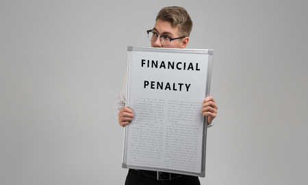 Portrait of a young man in a light shirt with a poster with an inscription about financial penalty in his hands isolated in a light Studio. Documents about Financial penalty. Form with a fine. insurance policy