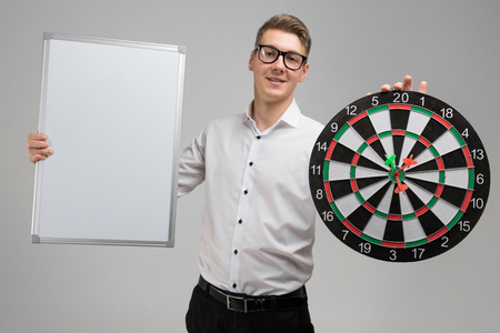handsome man in white shirt holds dartboard in middle and a white poster in his hands. insurance agent is alone in Studio. place for label