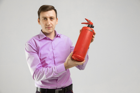 security guard with a fire extinguisher, isolated on white. Young Man Wearing Business Wear Standing in Studio Holding Fire Extinguisher and Looking at Camera. Security concept