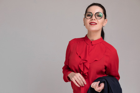 Portrait of a charming girl with glasses in the Studio on a white background. macrophotography friendly businesswoman in a red blouse and a black vest in her hands. Business concept. Concept of education