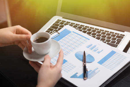 Close-up hands of business woman holding Cup of coffee and plate on background of financial documents. employee reads diagrams and drinks coffee in stylish modern office. Financial report with pie chart and womans hands with Cup of coffee
