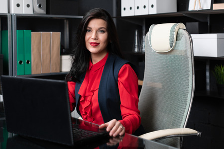 Businesswoman working at laptop computer in stylish office. woman lawyer in bright red blouse is receiving in his office. Business concept in modern world