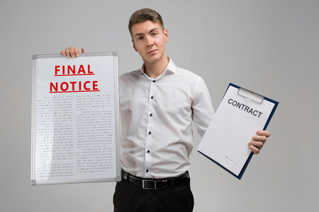 man in a shirt with a poster with a red inscription about final notice and contract isolated in a bright Studio. Holding Invoice With Final Demand Notification. FINAL EXAM message on the card shown by a man Stockfoto