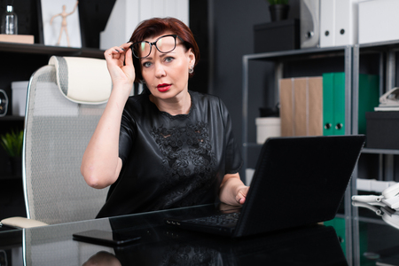 Adult woman at computer. portrait of Strict businesswoman holding hand glasses for laptop in modern office. Serious business woman working at laptop 스톡 콘텐츠