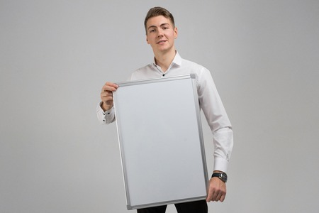 young businessman closed part of himself with white poster in his hands. Business young man in white shirt in bright Studio alone. place for label