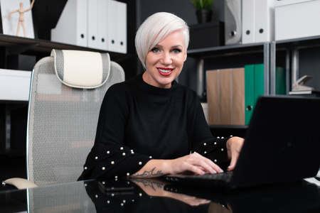 young girl with white short hair works at laptop with stylish modern office. Adult woman at computer. portrait of businesswoman in office at computer Desk