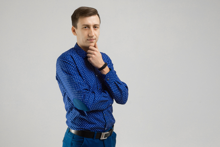 Confidence and business concept. close-up Portrait of Three quarters brooding successful young entrepreneur standing half-cocked in blue shirt isolated in Studio on white background