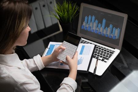 Gros plan mains tenant une calculatrice moderne sur fond graphique et ordinateur portable. Photo de concept d'entreprise, marché, bureau, taxe. Gros plan sur une femme d'affaires à l'aide d'une calculatrice et d'un ordinateur portable pour faire les calculs financiers sur un bureau en bois au bureau et une expérience de travail en entreprise