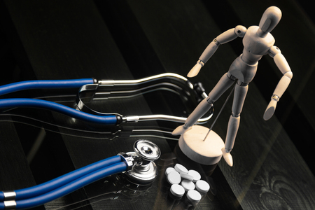 blue stethoscope and a pile of white pills lie next to figure of man on black background of a wooden table. Cardio therapist assistance, physical make cardiac physical. concept of medicine