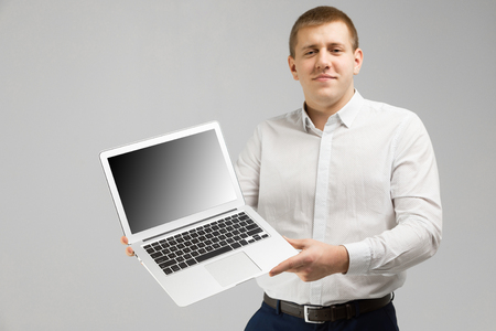 casual man showing blank laptop computer screen. Image of young man dressed in shirt isolated over white wall background. Looking camera while showing a display of a laptop computer