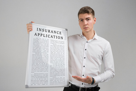 Portrait of a young man in a bright shirt with a poster of an application for insurance in his hands in isolation in light of the Studio. Life Insurance Form Application Security Concept. travel insurance form. insurance policy 版權商用圖片