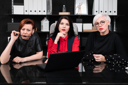 Entrepreneurs working at computer table. Three businesswomen work with laptop computer in modern office. group of business people with indignation on his face sitting in workspace in office Фото со стока