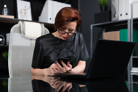 Adult woman at the computer. portrait of Strict businesswoman holding hand phone for laptop in modern office. Serious business woman working at laptop Stock Photo