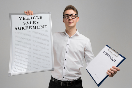 young man with a poster vehicle sales agreement is and blank contract form in his hands in isolation in light of the Studio. Vehicle Sales agreement document form. An concept Image of a vehicle sales agreement
