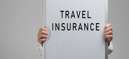 hands in shirt with a poster of travel insurance in isolation in light of the Studio. Concept meaning Be prepared for emergencies. travel insurance form. insurance policy