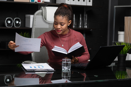 Concentrated Young African girl working in bright office.isolated Black businesswoman at work. Business concept in modern world