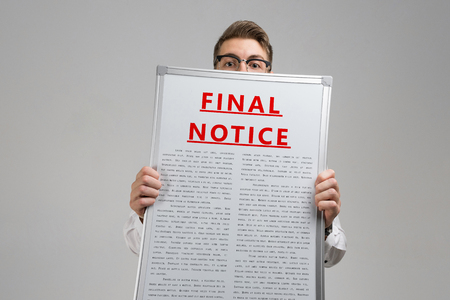 man in a shirt with a poster with a red inscription about final notice isolated in a bright Studio. Holding Invoice With Final Demand Notification. FINAL EXAM message on the card shown by a man