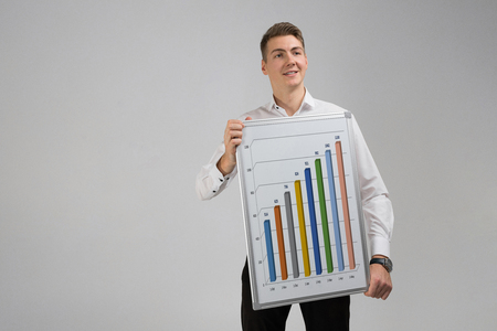 man in a shirt with a Board with statistics in his hands isolated in a light Studio. Graphics colorful for display white poster. Round, triangular, rising, falling and with percentages diagrams showing business progress and regression