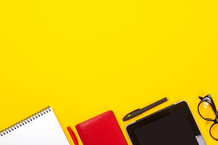 Office desk flat lay. Top view of working space table with glasses, notebook, tablet and stationery on colored yellow background. Back to school concept