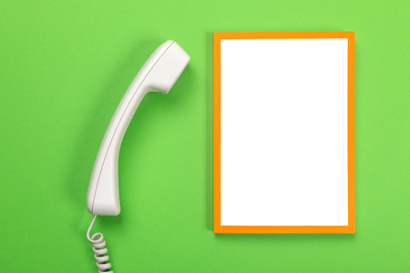 Working space table with telephone and frame with copyspace isolated on green background