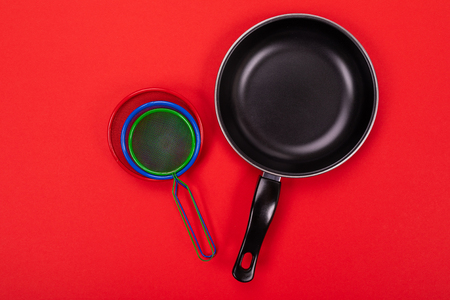 Close up picture of frying pan and several strainers on red background