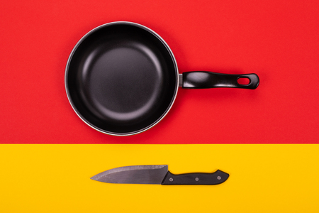 Empty frying pan isolated on red-yellow background with copyspace as cooking in kitchen concept Фото со стока