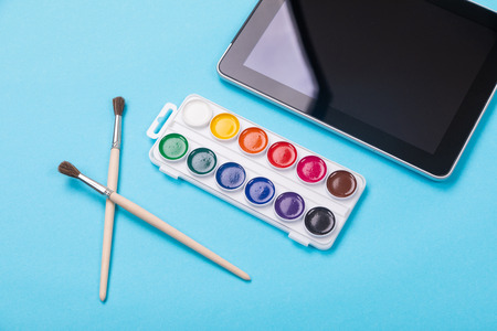 Watercolor paintbox. Color paints with paint brushes isolated on blue background as part of kids painting education concept Imagens