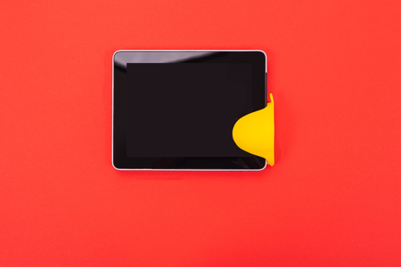 Tablet on kitchen with tableware as part of cooking online concept with copyspace on red background