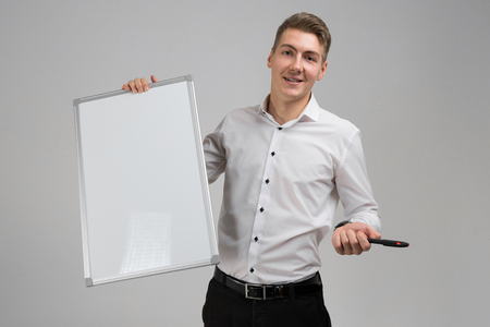 young businessman holding marker and white poster in his hands. Business young man in white shirt in bright Studio alone. place for label Banque d'images