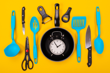 Different kitchen utensils for cooking in kitchen isolated on yellow background