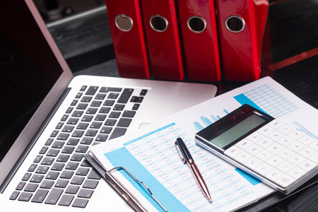 Business planning office Desk with laptop and financial documents next to red folders. Can be used as a business background. Financiers workplace