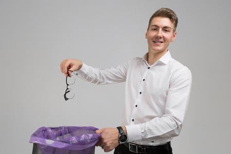 business man in white shirt holding glasses for vision over trash can and smiling. young man gets rid of his glasses. place for label